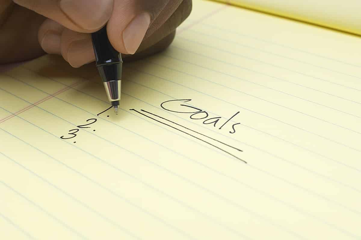 Person writing list of goals, close-up of hand