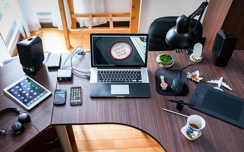 A desk with laptops, phones and gadgets